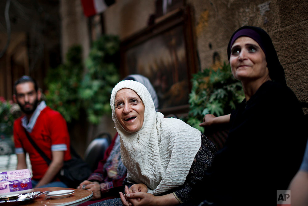 Palestinian residents Izdihar Abdul-Mahmoud, center, and her sister Hanan, right, spend their afternoon with neighbors outside their house on Lod street at the Palestinian refugee camp of Yarmouk in Damascus, Syria on July 16, 2018. Among the ruins of Yarmouk, the four Abdul-Mahmoud sisters survived seven years of conflict and siege. The district witnessed fighting between different insurgent groups as well as intense government bombardment and a tight siege that left residents on the verge of starvation. (AP Photo/Hassan Ammar)