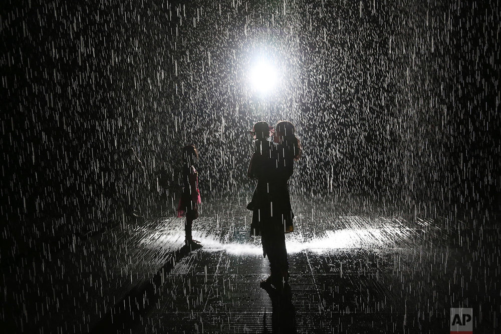 "Visitors walk through the Sharjah Art Foundation's ""Rain Room"" installation in Sharjah, United Arab Emirates, Sunday, July 22, 2018. The art installation uses motion sensors to allow visitors to walk through it without getting wet as 2,500 liters of self-cleaning recycled water fall. (AP Photo/Jon Gambrell)"