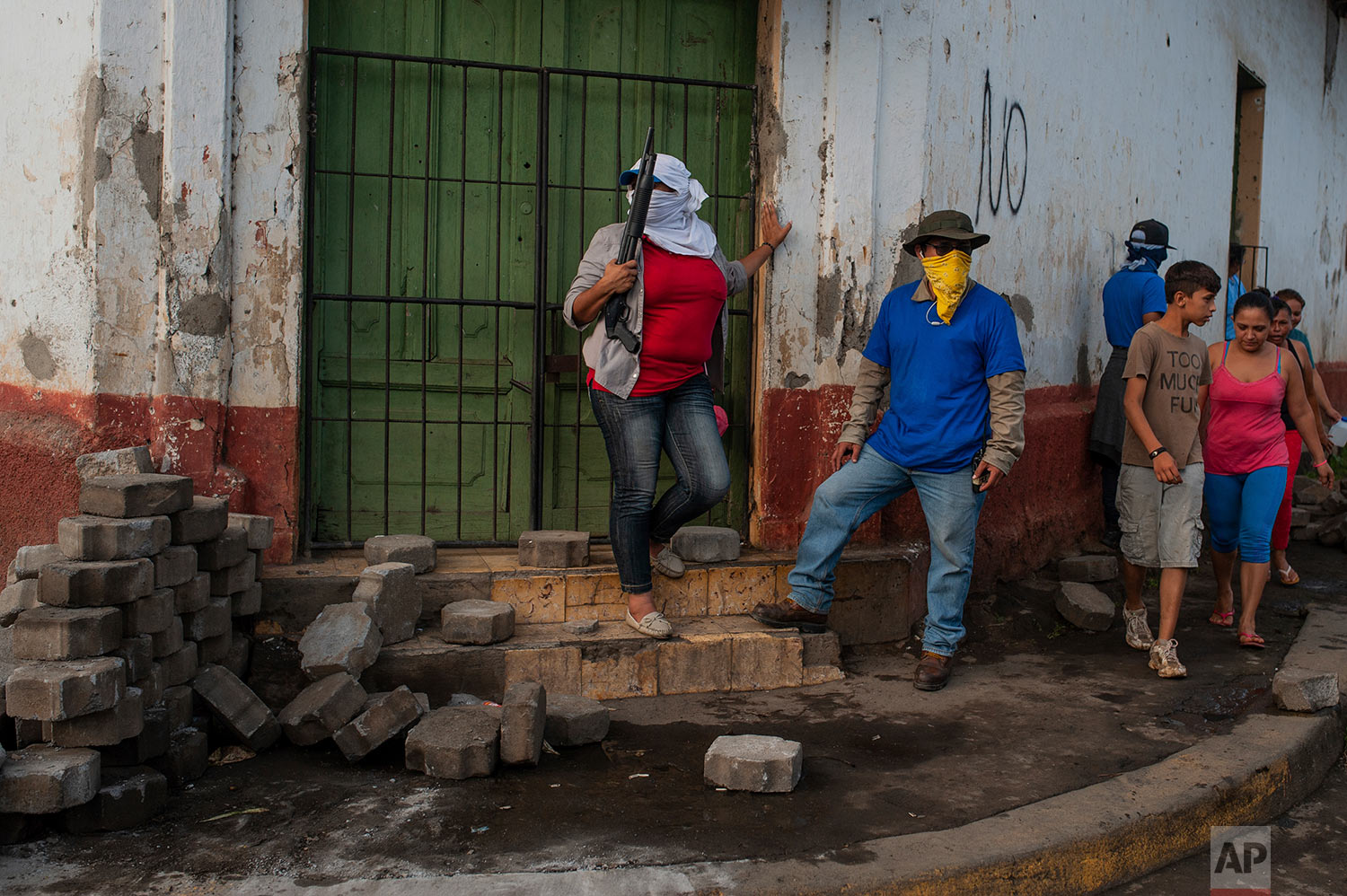 Pro-government Sandinista militia members stand guard at a torn down barricade, which had been set up by anti-government protesters, after police and militias stormed the Monimbo neighborhood of Masaya, Nicaragua, July 17, 2018. Heavily armed police and militias laid siege to and then retook a symbolically important neighborhood that had recently become a center of resistance to President Daniel Ortega's government. (AP Photo/Cristobal Venegas)