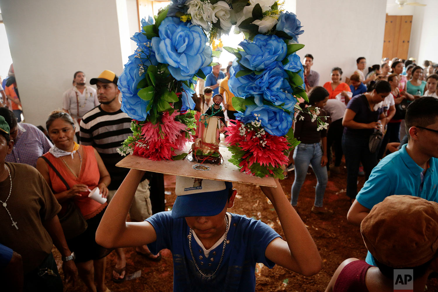 A youth holds up a statue of Santo Domingo de Guzman inside Las Sierritas church during Mass in honor of the saint in Managua, Nicaragua, July 31, 2018. The festival has its roots in the 1885 discovery of the 8-centimeter (a little over 3-inch) statue of Santo Domingo de Guzman, also known as St. Dominic de Guzman, the founder of the Dominican religious order. (AP Photo/Arnulfo Franco)