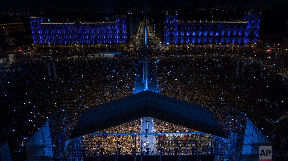 People pack Mexico City's main square, the Zocalo, as presidential candidate Andres Manuel Lopez Obrador delivers his victory speech, July 1, 2018. Lopez Obrador has claimed victory in Mexico's presidential election, calling for reconciliation. (AP Photo/Christian Palma)