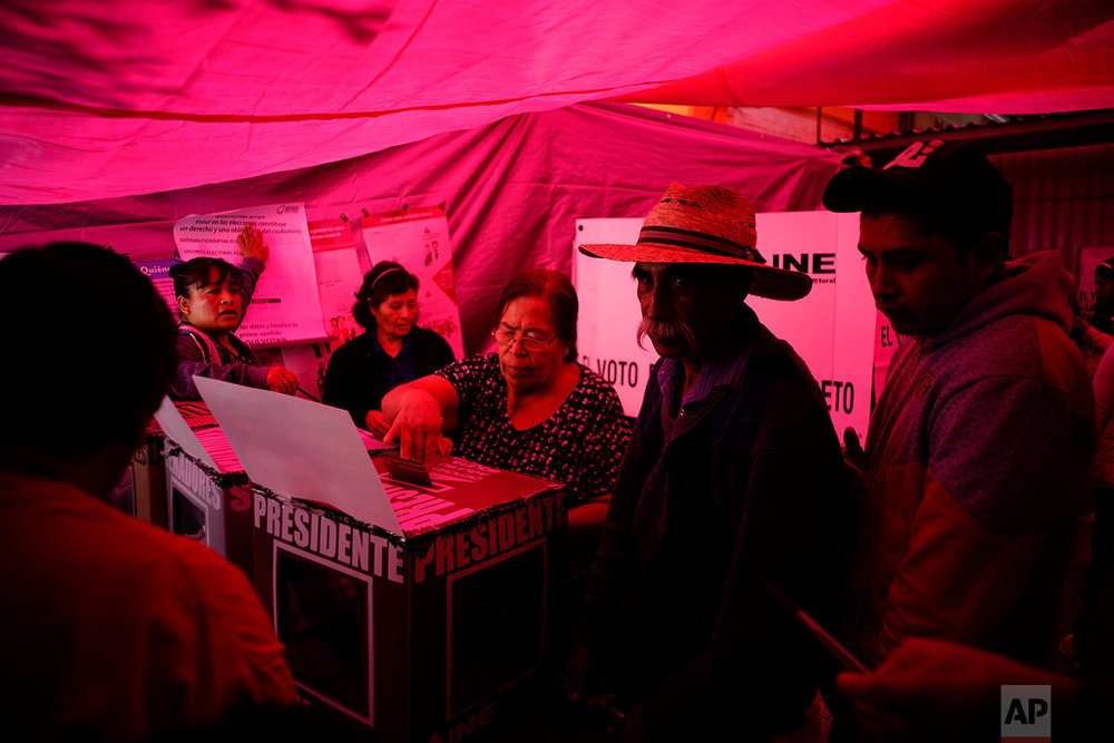 A woman casts her ballot at a voting center covered by a red tarp, during general elections in Iztapalapa, Mexico City, July 1, 2018. Sunday's elections for posts at every level of government are Mexico's largest ever and have become a referendum on corruption, graft and other tricks used to divert taxpayer money to officials' pockets and empty those of the country's poor. (AP Photo/Ramon Espinosa)