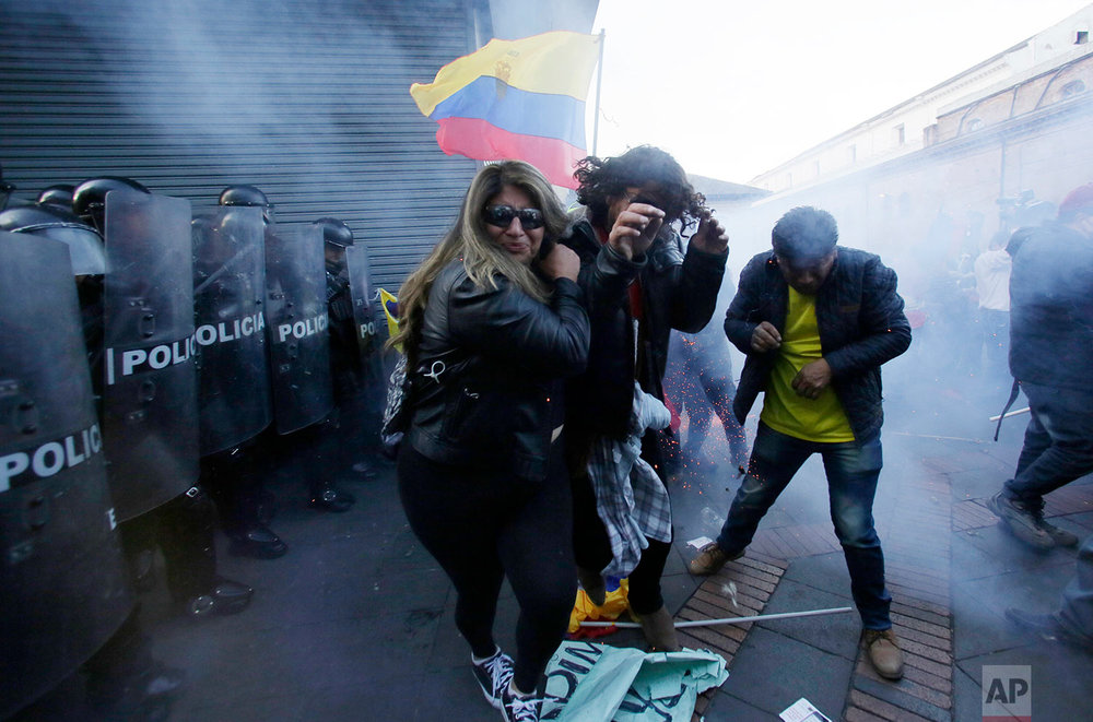 Supporters of Ecuador's former President Rafael Correa clash with police near the government palace during a rally in support of Correa after a judge ordered him jailed for failing to appear in court as required as part of a kidnapping probe, in Quito, Ecuador, July 5, 2018. (AP Photo/Dolores Ochoa)