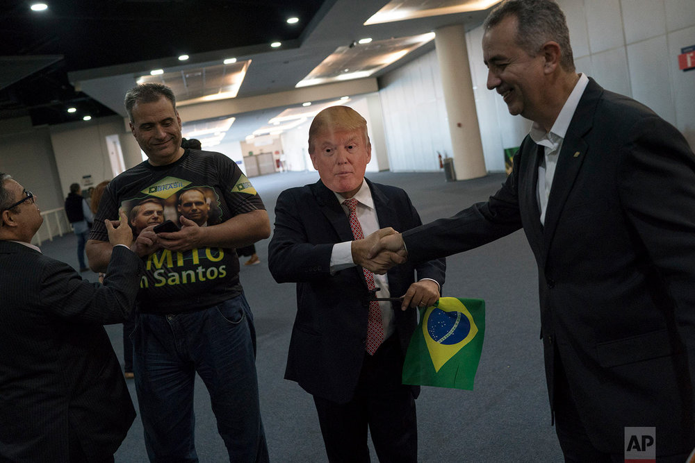 A supporter of Brazil's presidential candidate Jair Bolsonaro, wearing a mask of President Donald Trump, arrives to the National Social Liberal Party convention where Bolsonaro is to accept the nomination in Rio de Janeiro, Brazil, July 22, 2018. Far-right congressman Bolsonaro is running in distant second to former President Luiz Inacio Lula da Silva, who is in jail, and promises to clean house ahead of October elections. (AP Photo/Leo Correa)