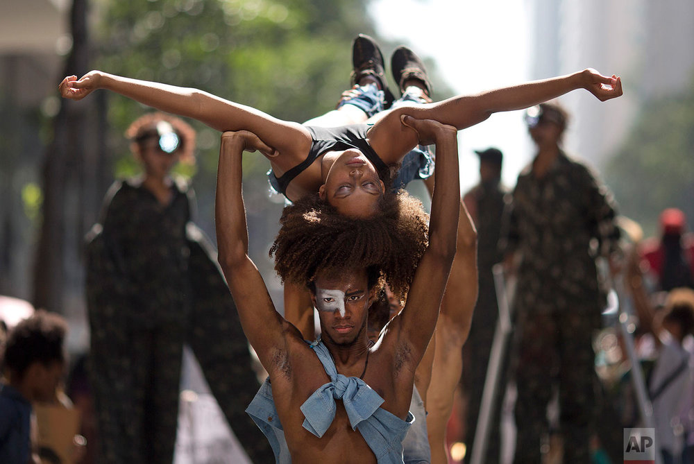 """Performers protest violence against black people in Rio de Janeiro, Brazil, July 23, 2018. Activists and relatives of black youth who have been killed in Rio de Janeiro marched to demand justice, as they marked the 25th anniversary of the """"Candelaria Massacre"""" when eight black youths were killed by police. (AP Photo/Silvia Izquierdo)"""