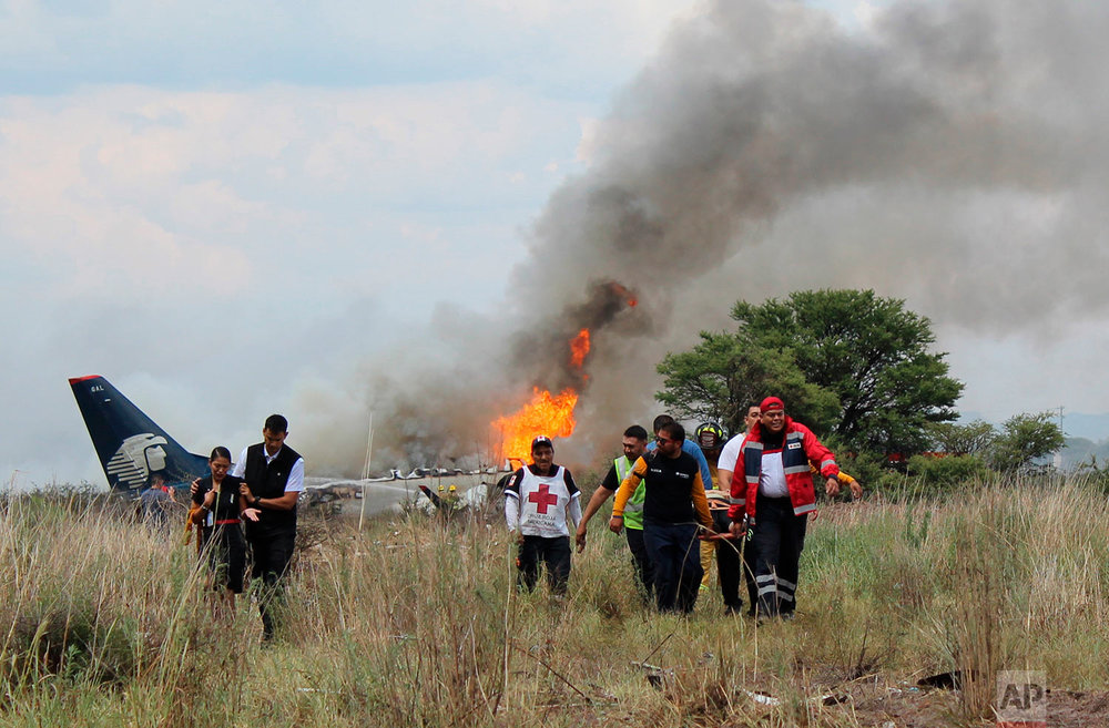 In this photo released by Red Cross Durango communications office, Red Cross workers and rescue workers carry an injured person on a stretcher, right, as airline workers, left, walk away from the site where an Aeromexico airliner crashed in a field near the airport in Durango, Mexico, July 31, 2018. The jetliner crashed while taking off during a severe storm, smacking down in a field nearly intact then catching fire, and officials said it appeared everyone on board escaped the flames. (Red Cross Durango via AP)