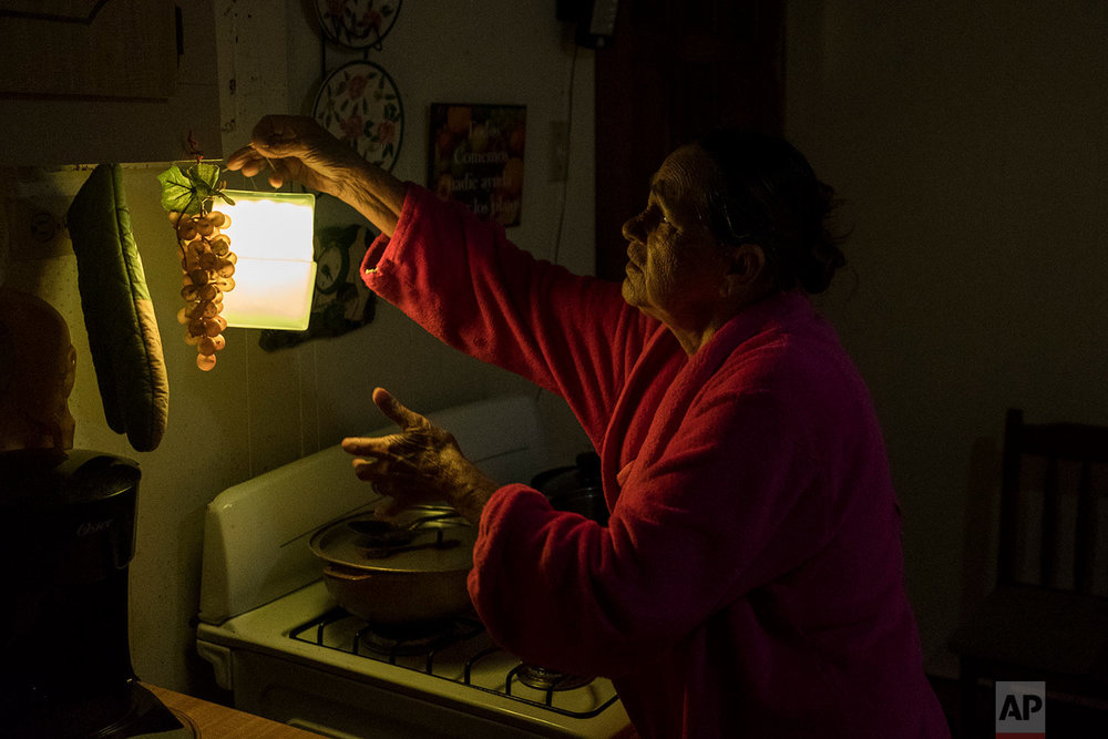 Marta Bermudez Robles hangs a lamp in her kitchen in Adjuntas, Puerto Rico, at her home that is still with electricity since Hurricane Irma and Maria, July 12, 2018. The only power Bermudez and her husband have had for 10 months is courtesy of a neighbor who threw over an extension cord connected to his generator that provides just enough power to light one bulb in the kitchen and another in the living room for a couple hours each day. (AP Photo/Dennis M. Rivera Pichardo)