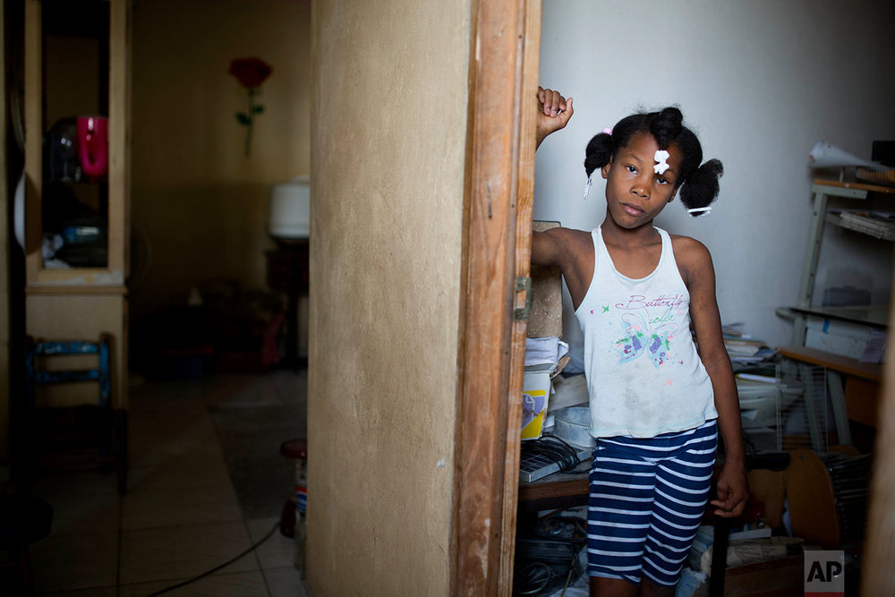 In this June 30, 2018 photo published in July, foster girl Franchina, 11, poses for a picture at the entrance of her room at her foster parent home in Port-au-Prince, Haiti. Franchina's foster parents cared for one troubled foster child, an 11-year-old named Alexandre, for six months, and now have Franchina living with them. (AP Photo/Dieu Nalio Chery)