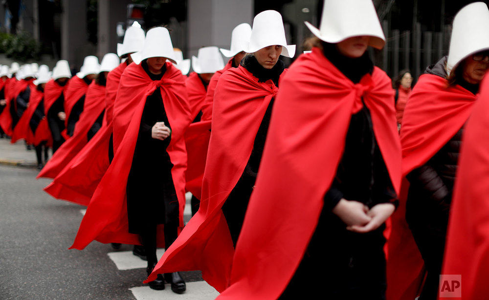"""Women in favor of a measure to expand legal abortions wear red cloaks and white bonnets like the characters from the novel-turned-TV series """"The Handmaid's Tale"""" as they march in silence to Congress in Buenos Aires, Argentina, July 25, 2018. Once they reached Congress, one of them read a letter by """"Handmaid's Tale"""" author Margaret Atwood, who supports the effort led by Argentine feminist groups. (AP Photo/Natacha Pisarenko)"""
