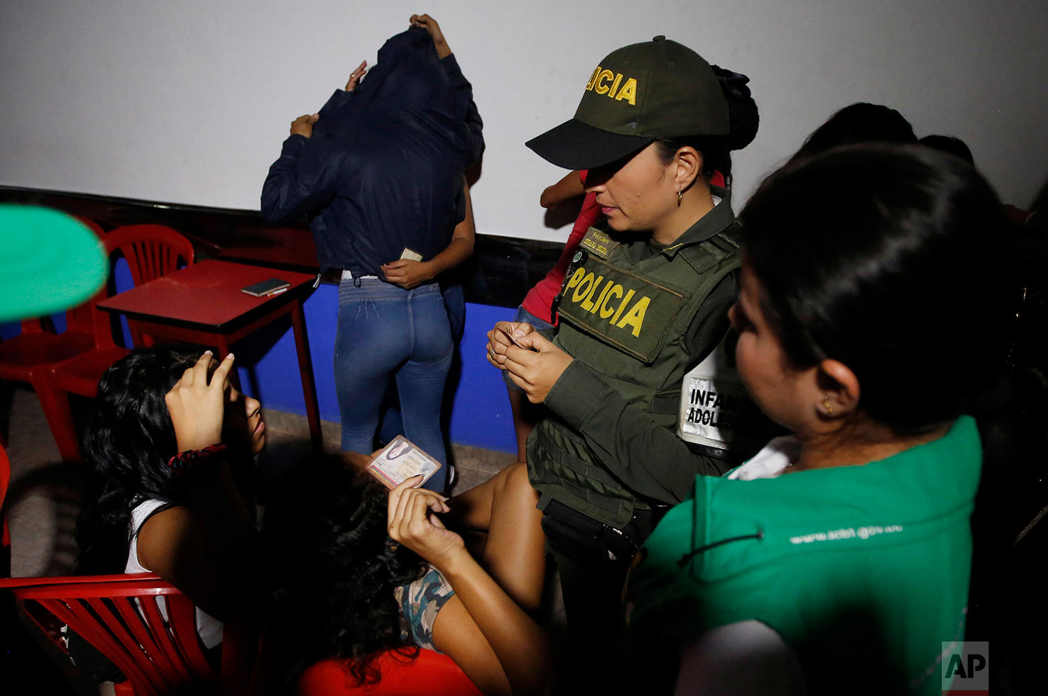 In this June 26, 2018 photo published in July, police look at the identification cards of Venezuelan girls to check their ages as they search for minors at a bar known for prostitution in Cucuta, Colombia, as two females hide from the camera, behind. As Venezuelans flee their country's collapsing economy and an autocratic government in rising numbers, a grim toll is becoming evident among the youngest arrivals: Children are sleeping on the streets, suffering from hunger and untreated infections, and sometimes being lured into sex work. (AP Photo/Fernando Vergara)
