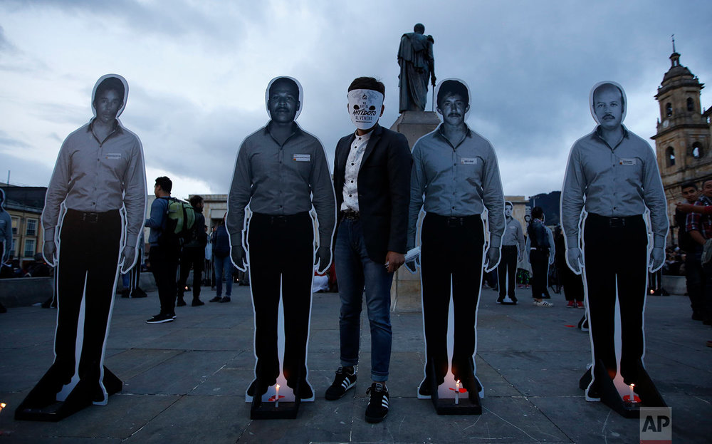 A demonstrator poses between life-sizes cutouts of slain activists during a candle light vigil honoring activists killed since the signing of the peace accords in Bogota, Colombia, July 6, 2018. (AP Photo/Fernando Vergara)