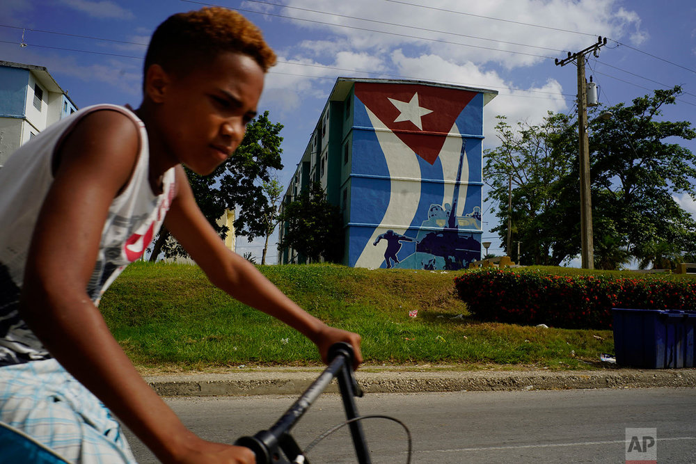 A youth rides past a mural of a Cuban flag and Fidel Castro jumping off a tank during the Bay of Pigs invasion in Guantanamo, Cuba, July 25, 2018.