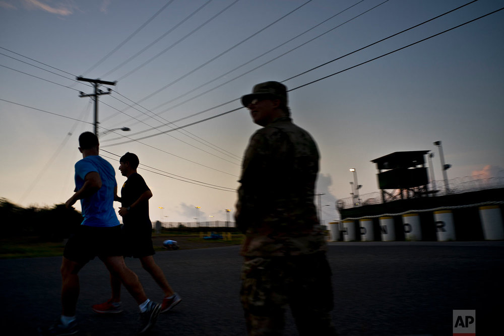 A U.S. soldier stands guard at Camp Delta as other soldiers jog past on the naval base at Guantanamo Bay, June 6, 2018.