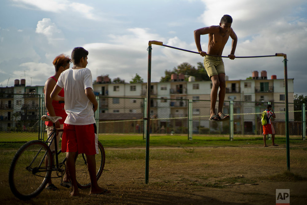 A youth works out on an exercise bar at a park by Plaza de la Revolucion in Guantanamo, Cuba, July 24, 2018.