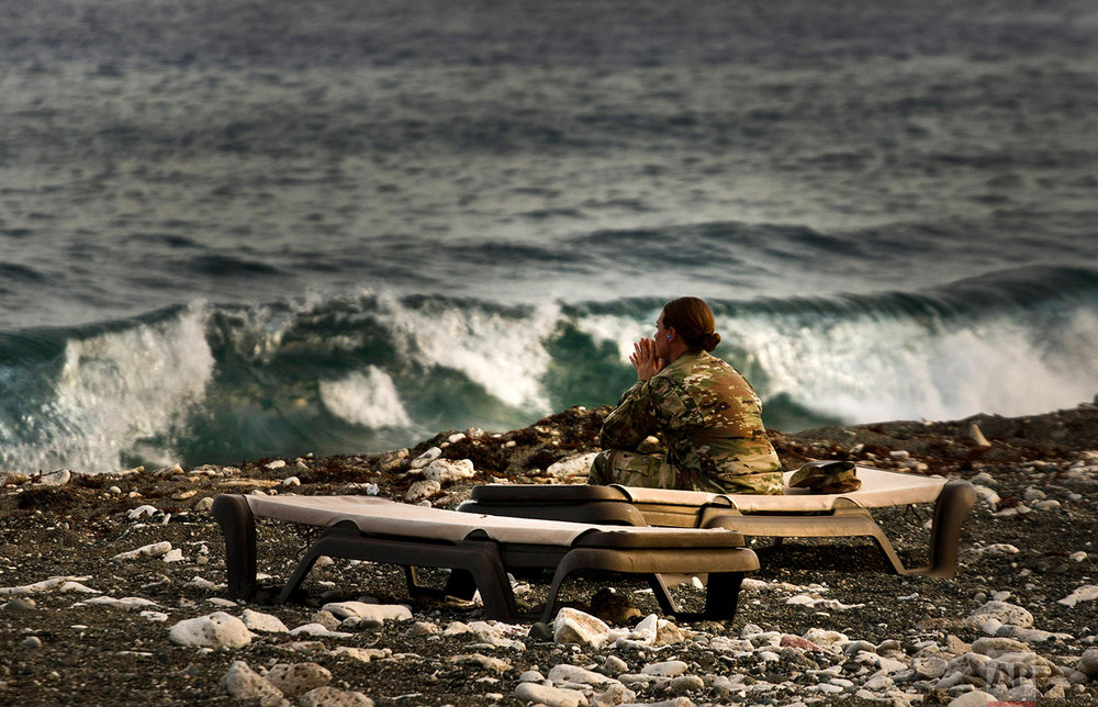 A female U.S. army soldier spends a quiet moment looking out at the ocean from the naval base at Guantanamo Bay, June 6, 2018.