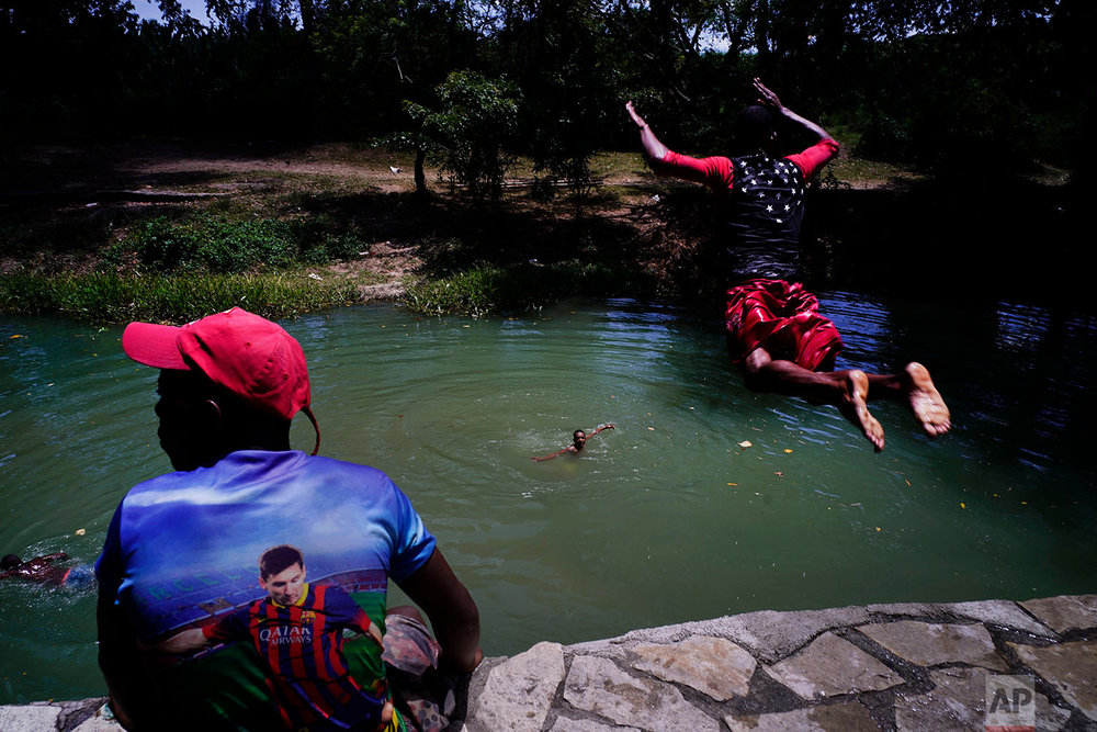 A youth jumps into the Bano River in Guantanamo, Cuba, July 25, 2018. The shirt at left features Barcelona soccer player Lionel Messi.