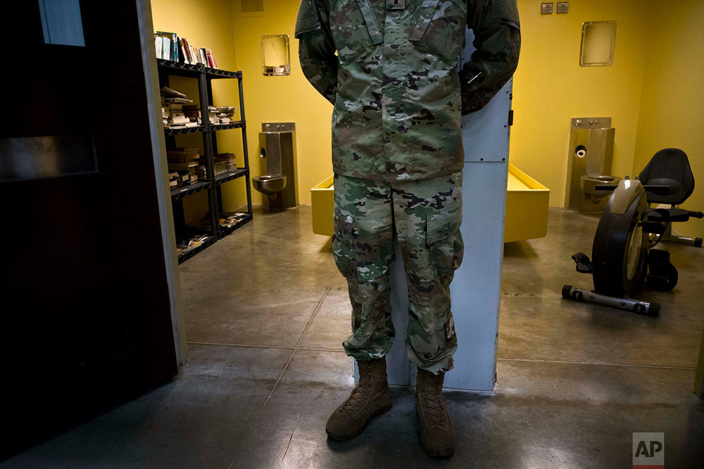 A U.S. soldier stands between cells used as a library and gym inside Camp VI at the naval base at Guantanamo Bay, June 6, 2018.