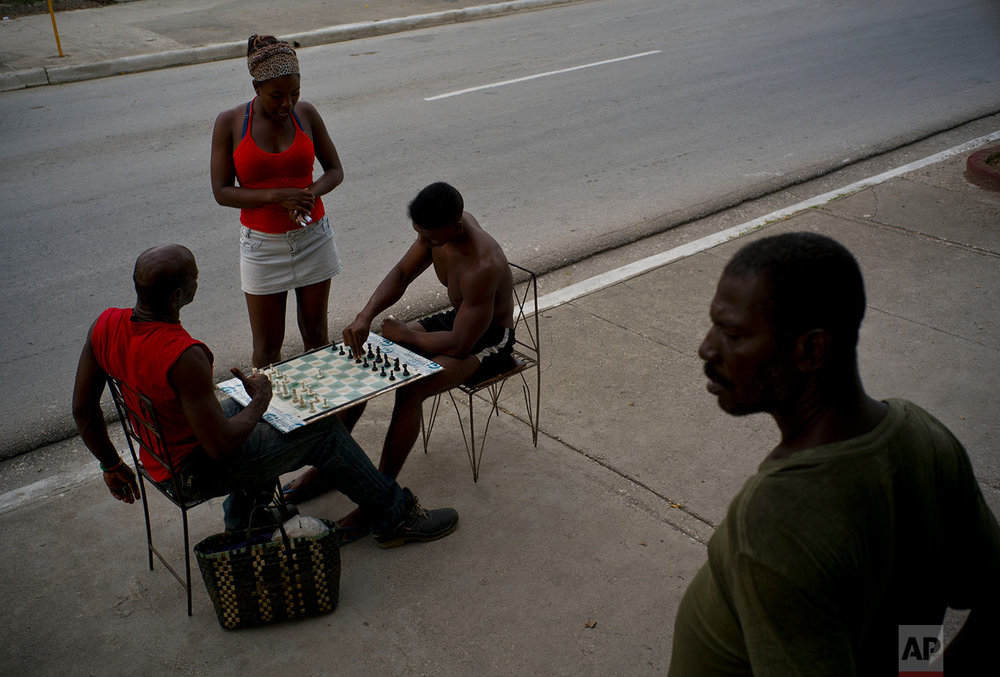 Men playing chess as another stands outside his home on a hot afternoon in Guantanamo, Cuba, July 24, 2018.