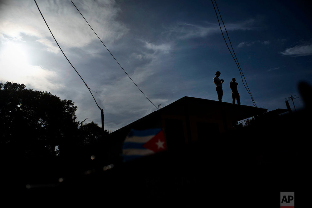 Men stand on a home's roof to cool off in in Guantanamo, Cuba, July 24, 2018.
