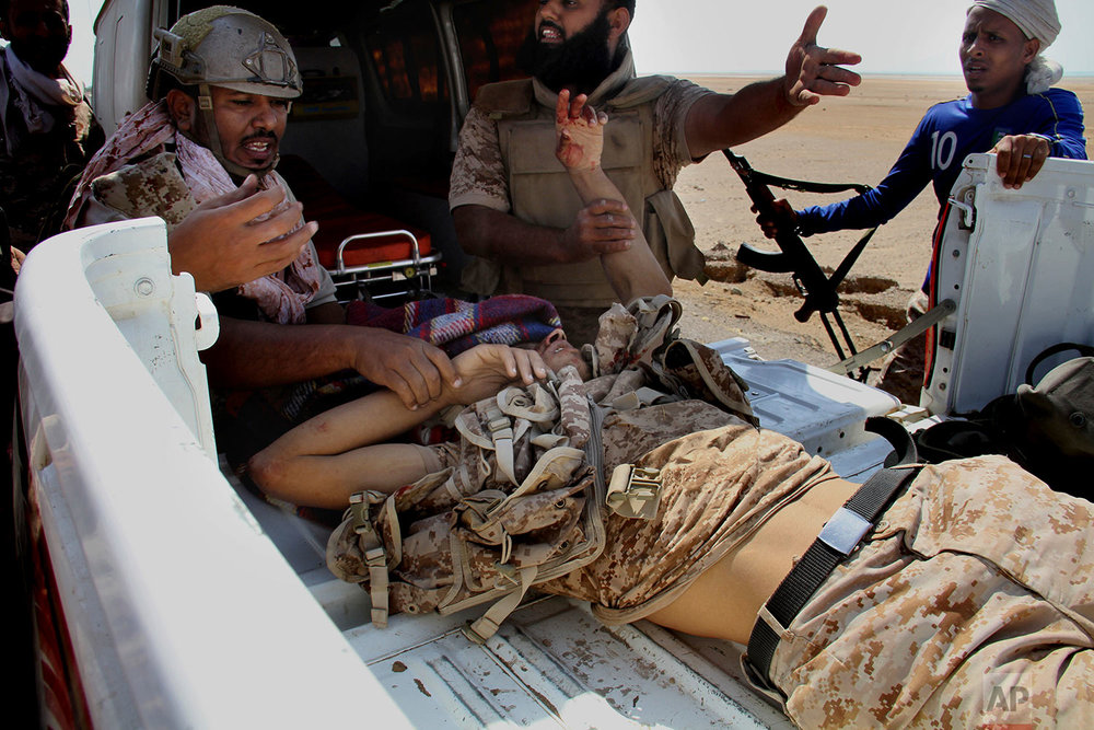 Coalition-backed fighters help a wounded man during an advance on Yemen's Red Sea port town of Mocha. (AP Photo)