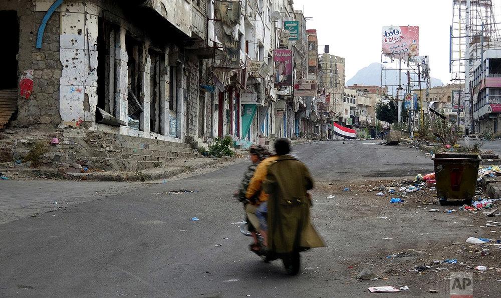 Men make their way through damages in Taiz, Yemen. (AP Photo)