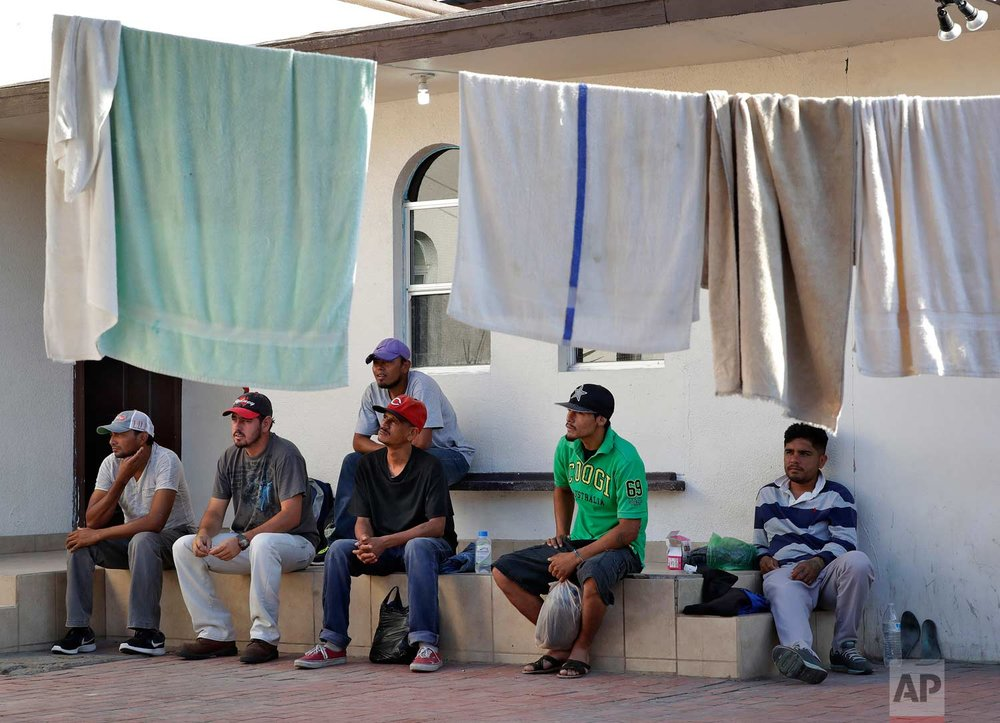 "Central American men sit in the courtyard of the Asociacion Casa Del Migrante ""La Divina Providencia"" group house as their laundry dries Thursday, July 19, 2018 in San Luis, Sonora, Mexico. (AP Photo/Matt York)"