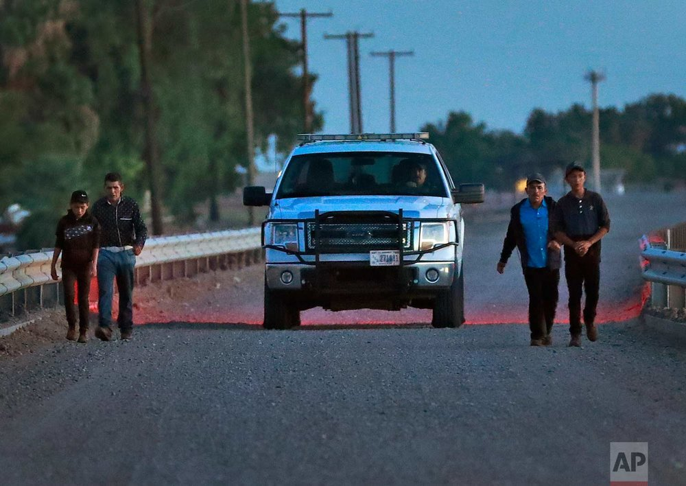 A U.S. Customs and Border Patrol agent, center in truck, escorts four Guatemalan nationals consisting of two men and a pair of 12 and 13-year-old boys, after they self-surrendered, to a holding vehicle Wednesday, July 18, 2018 along the international border in Yuma, Ariz. (AP Photo/Matt York)