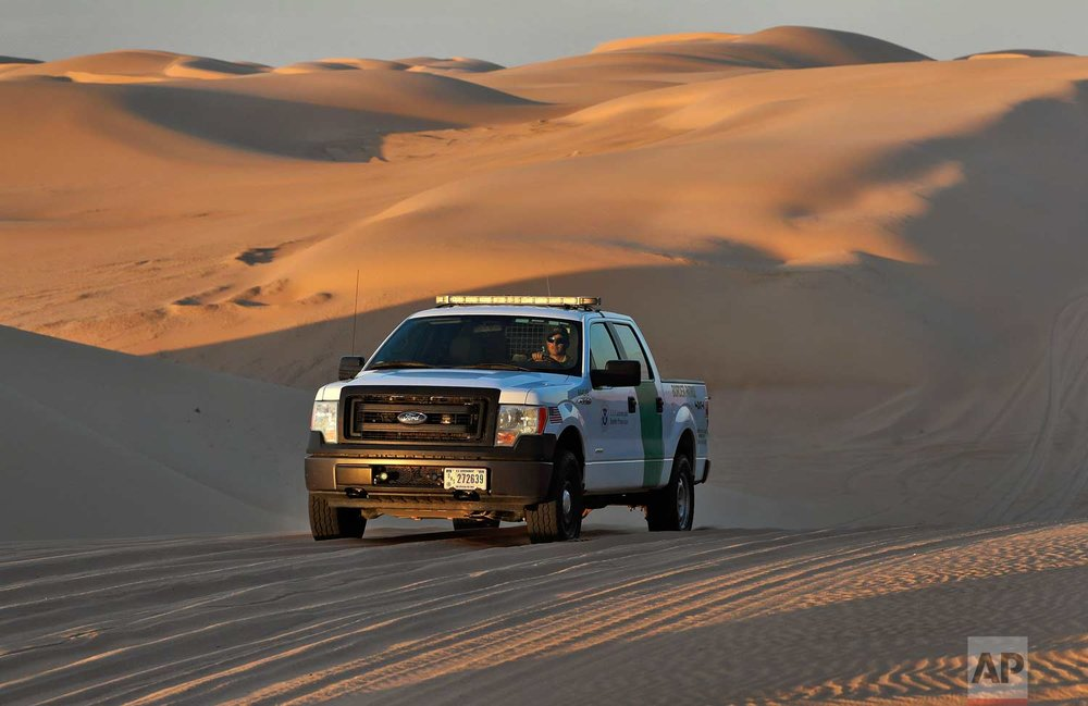 A U.S. Customs and Border Patrol agent patrols a area of sand dunes Wednesday, July 18, 2018 along the international border with Mexico in Imperial County, Calif. (AP Photo/Matt York)