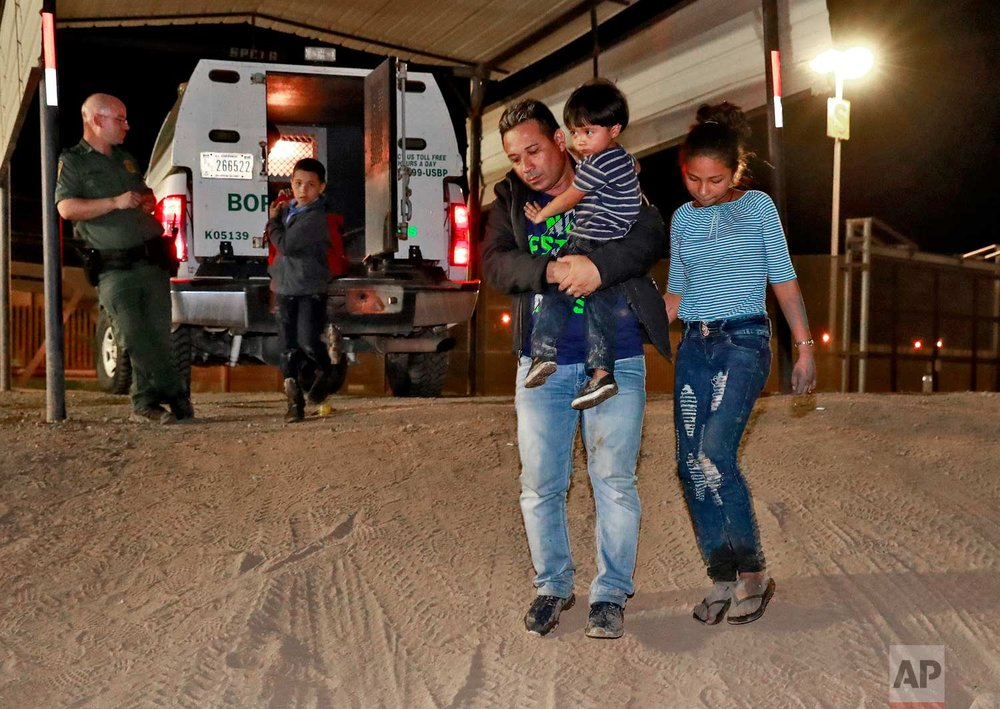 A Honduran man carries his 3-year-old son as his daughter and other son follow to a transport vehicle after being detained by U.S. Customs and Border Patrol agents Wednesday, July 18, 2018 in San Luis, Ariz. (AP Photo/Matt York)