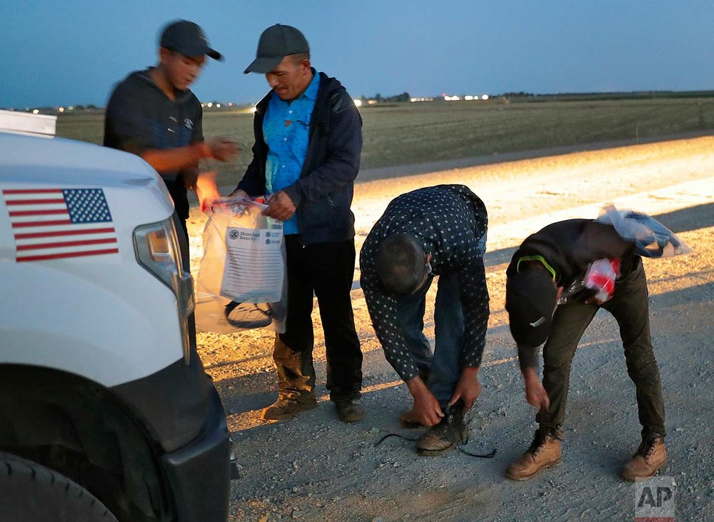 Four Guatemalan nationals consisting of two men and a pair of 12 and 13-year-old boys, remove their shoe laces and personal itmes after being arrested by a U.S. Customs and Border Patrol agent Wednesday, July 18, 2018 in Yuma, Ariz.(AP Photo/Matt York)