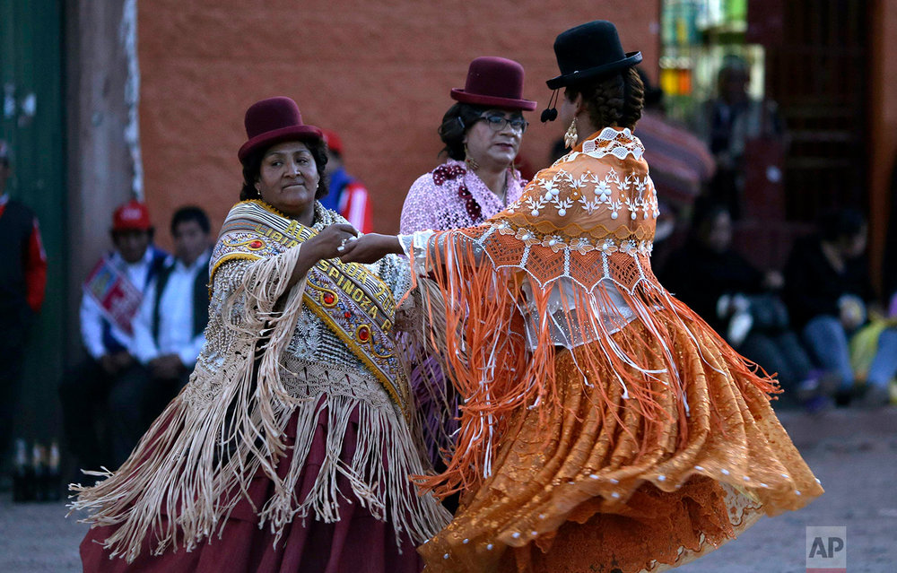 Festival founder Libia Espinoza, left, dances with transgenders Coco and Jessi during festivities honoring Our Lady of Copacabana, in Cuzco, Peru, Aug. 5, 2018. (AP Photo/Martin Mejia)