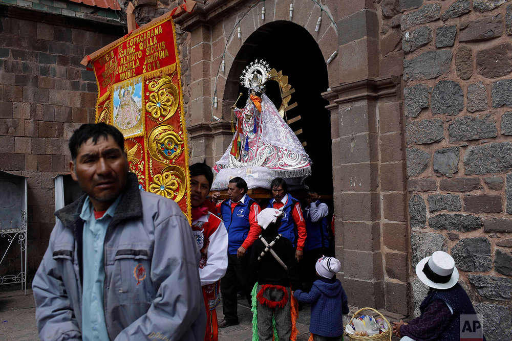 """Cargadores"" or male carriers exit the Almudena Temple shouldering a statue of Our Lady of Copacabana, where a service was held in the virgin's honor, in Cuzco, Peru, Aug. 5, 2018. (AP Photo/Martin Mejia)"
