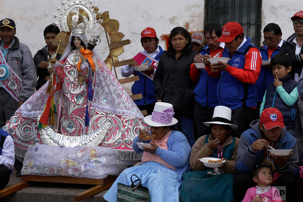 """Cargadores"" or male carriers and devotees lunch on free bowls of beef and wheat soup during a pause in the religious procession honoring Our Lady of Copacabana, in Cuzco, Peru, Aug. 5, 2018. (AP Photo/Martin Mejia)"