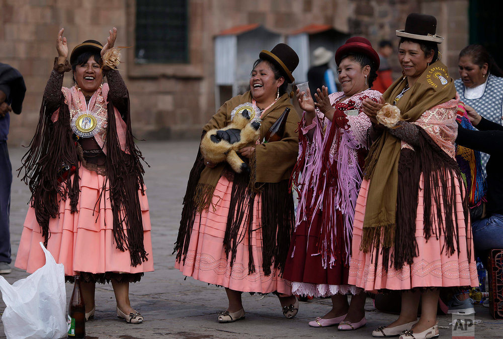 """Chola"" dancers, easily identifiable by their typical Aymara dress: wide skirts, bowler hats and elaborate shawls, applaud the fancy footwork of a couple, as they take a break from their performance honoring Our Lady of Copacabana, in Cuzco, Peru, Aug. 5, 2018. (AP Photo/Martin Mejia)"