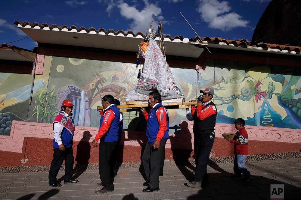 """Cargadores"" or male carriers walk with a statue of Our Lady of Copacabana belonging to resident Libia Espinoza, in a religious procession honoring the Bolivian virgin, in Cuzco, Peru, Aug. 5, 2018. (AP Photo/Martin Mejia)"