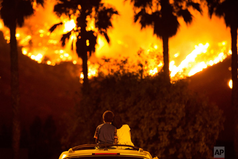 Princess Bass, 5, rests her head on the shoulder of her brother, King, 6, as they sit and watch the Holy Fire burn from on top of their parents' car Thursday night, Aug. 9, 2018 in Lake Elsinore, Calif. More than a thousand firefighters battled to keep a raging Southern California forest fire from reaching foothill neighborhoods Friday before the expected return of blustery winds that drove the flames to new ferocity a day earlier. (AP Photo/Patrick Record)