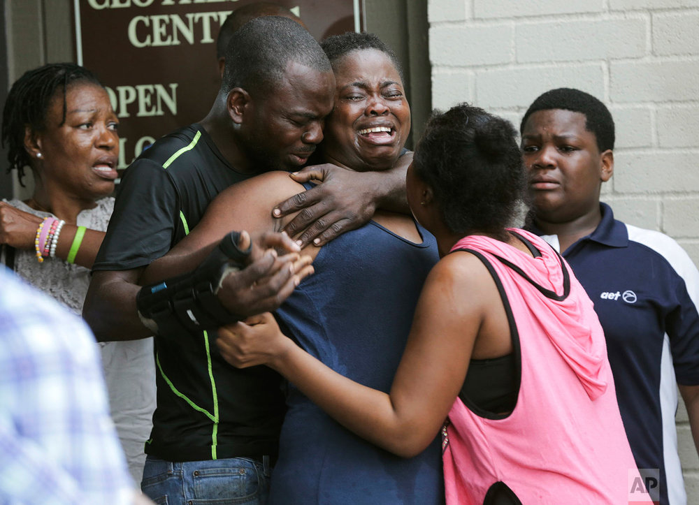 The mother, center, of two young children is comforted after she found them stabbed to death in their father's apartment in Houston on Saturday, Aug. 4, 2018. Authorities say that Jean Pierre Ndossoka, the man suspected of fatally stabbing his two children, has been hospitalized after police found him Sunday with a self-inflicted gunshot wound in his car. Court records show he has been charged with capital murder. (Elizabeth Conley/Houston Chronicle via AP)