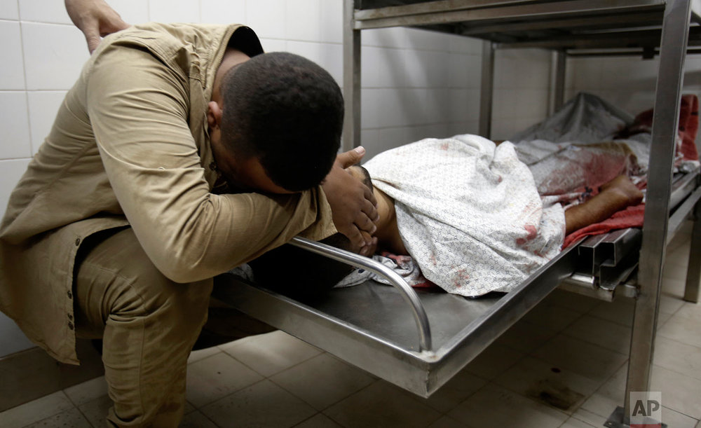 A relative mourns over the body of Abdullah al-Qutati, 26, at the morgue of the European hospital east of Khan Younis, southern Gaza Strip, east of Khan Younis, Friday, Aug. 10, 2018. Two Palestinians, including a paramedic, were shot and killed by Israeli fire at a Hamas-led protest along the border, Gaza's Health Ministry said. (AP Photo/Adel Hana)