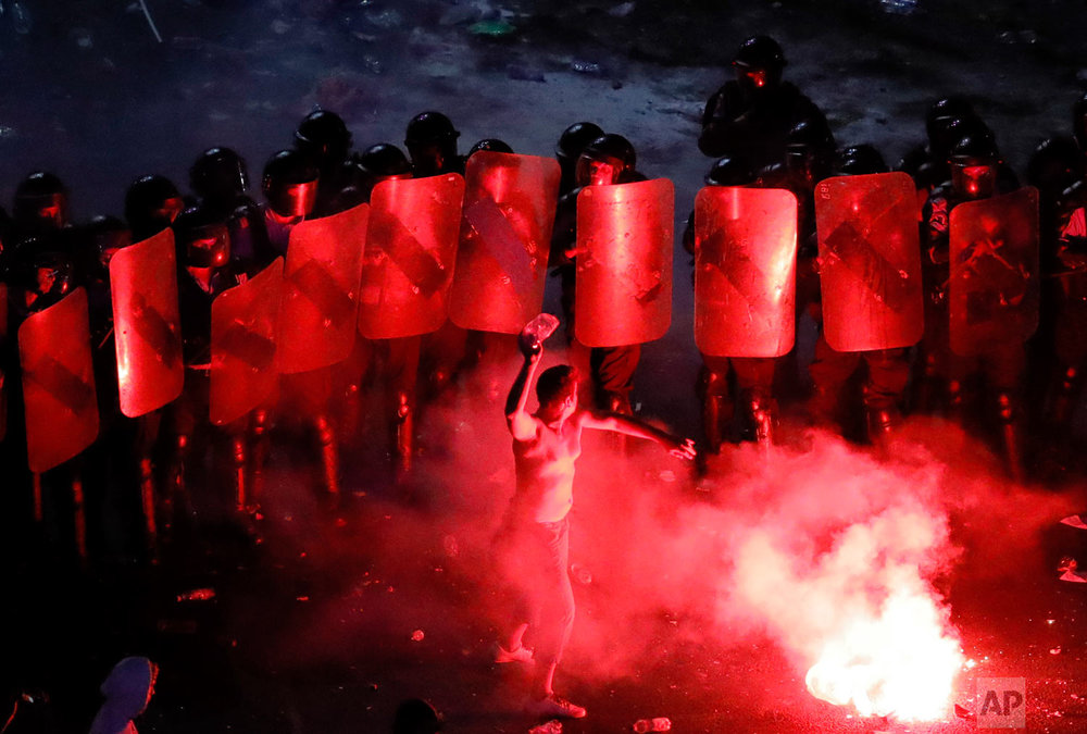 A man throws a plastic bottle at riot police during protests outside the government headquarters, in Bucharest, Romania, Friday, Aug. 10, 2018. Tens of thousands of Romanians flocked to an anti-government protest in Bucharest on Friday, urging the left-wing government to resign and call an early election. (AP Photo/Vadim Ghirda)