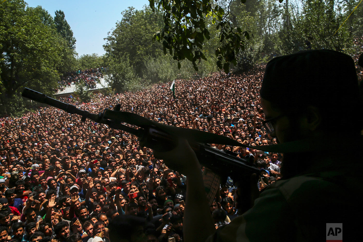A Kashmiri rebel fires his gun to salute fallen comrades during their joint funeral in Malikgund village, south of Srinagar, Indian controlled Kashmir, Saturday, Aug. 4, 2018. At rebels and an Indian army soldier were killed in gunbattles in disputed Kashmir, triggering violent protests by residents opposed to Indian rule, officials said Saturday. (AP Photo/Dar Yasin)