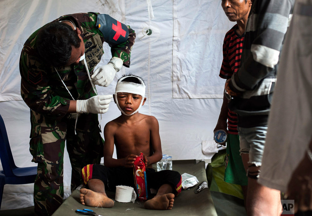 A military paramedic tends to a boy who's head was injured from Sunday's earthquake at a makeshift hospital in Kayangan, Lombok Island, Indonesia, Wednesday, Aug. 8, 2018. The north of Lombok has been devastated by the magnitude 7.0 quake that struck Sunday night, damaging thousands of buildings and killing dozens. (AP Photo/Fauzy Chaniago)