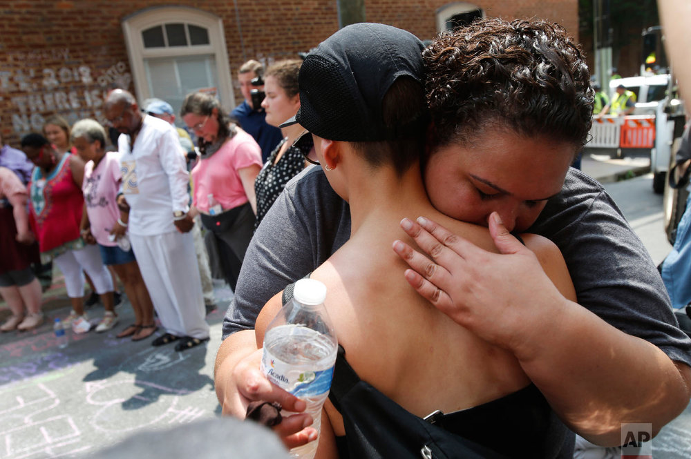 A couple embrace as they participate in prayers at the intersection where Heather Heyer was killed last year as they mark the anniversary of the Unite the Right rally in Charlottesville, Va., Sunday, Aug. 12, 2018. On that day, white supremacists and counterprotesters clashed in the city streets before a car driven into a crowd struck and killed Heyer. (AP Photo/Steve Helber)