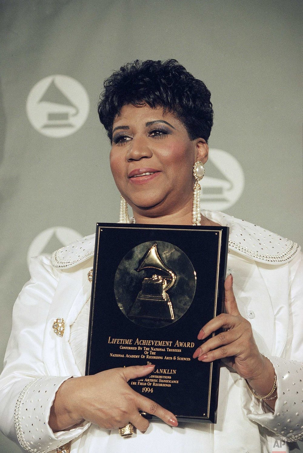 Aretha Franklin holds her award for lifetime achievement backstage at the 36th Annual Grammy Awards ceremonies at New York's Radio City Music Hall, March 1, 1994. (AP Photo/Mike Albans)