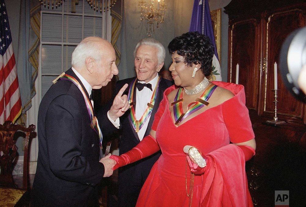 Singer Aretha Franklin listens to composer Morton Gould, as actor Kirk Douglas looks on following a dinner at the State Department in Washington, Saturday, Dec. 3, 1994. (AP Photo/Doug Mills)