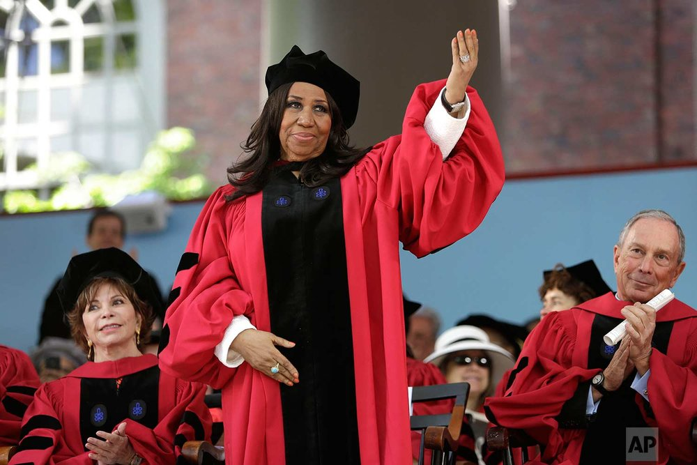Singer Aretha Franklin waves while standing to receive an honorary Doctor of Arts degree as Chilean author Isabel Allende, left, and former Mayor of New York City Michael Bloomberg, right, look on during Harvard commencement ceremonies, Thursday, May 29, 2014, in Cambridge, Mass. (AP Photo/Steven Senne)