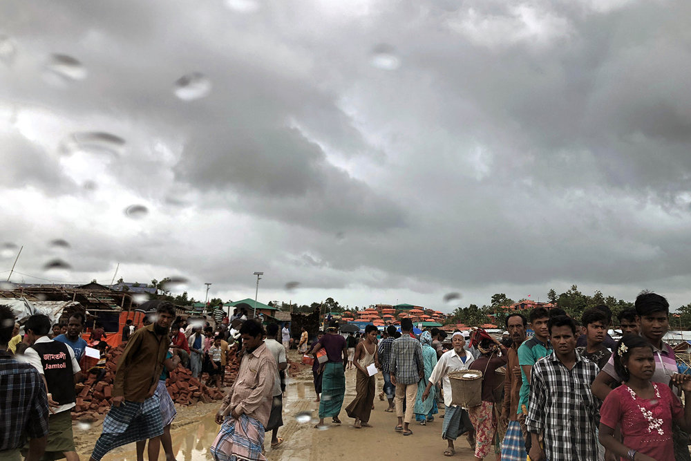 Rohingya refugees walk on a muddy road in the rain through the Jamtoli refugee camp in Bangladesh on Tuesday, June 26, 2018. (AP Photo/Wong Maye-E)