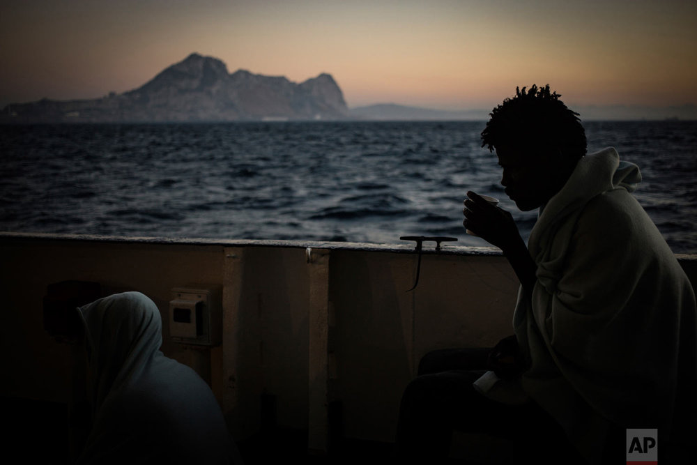In this photo taken Thursday, Aug. 9, 2018, migrants stand on the deck of the Open Arms boat, after being rescued off the coast of Libya in the early hours of the nigh of Thursday, Aug. 2, 2018. (AP Photo/Valerio Nicolosi)