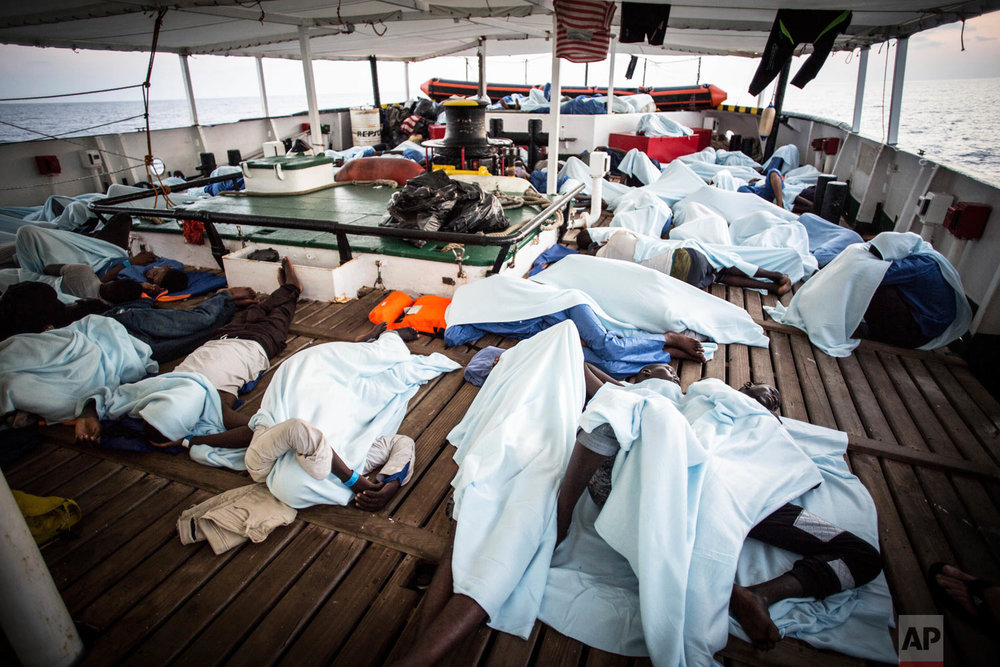 In this photo taken Thursday, Aug. 2, 2018, migrants rest on the deck of the Open Arms boat, after being rescued off the coast of Libya in the early hours of the night. (AP Photo/Valerio Nicolosi)