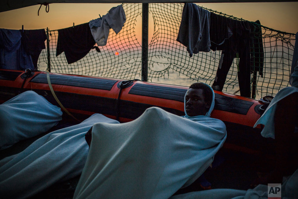 In this photo taken Friday, Aug. 3, 2018, migrants rest on the deck of the Open Arms boat, after being rescued off the coast of Libya in the early hours of the nigh of Thursday, Aug. 2, 2018. (AP Photo/Valerio Nicolosi)