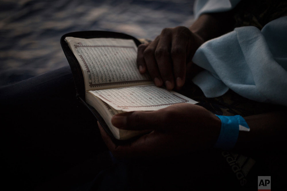 In this photo taken Friday, Aug. 3, 2018, a migrants reads a prayer book on the deck of the Open (AP Photo/Valerio Nicolosi)